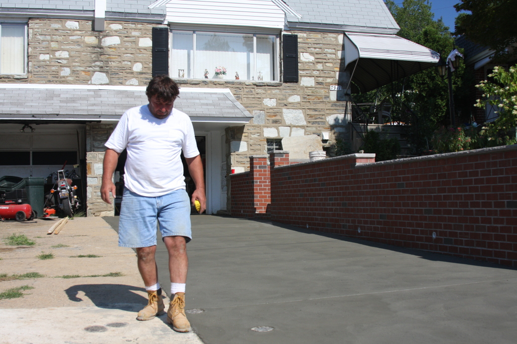 Concrete driveway and brick retaining wall by M and C Contractors